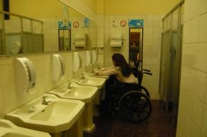 Fotografia del taller que muestra a persona usando una silla de ruedas en un baño lavándose las manos