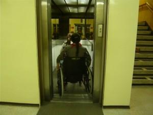Fotografia del taller que muestra a persona usando una silla de ruedas para entrar a un ascensor