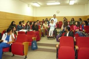 Fotografía que muestra expositor del programa y asistente usando silla de ruedas